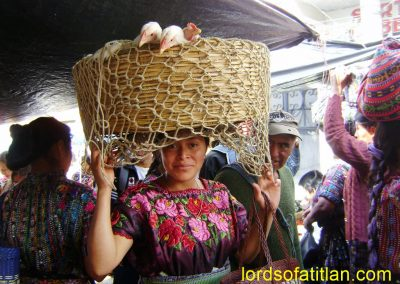 Chickens spying woman from Santa Clara. Likewise, she caught the attention of man behind. Market of Sololá Sololá