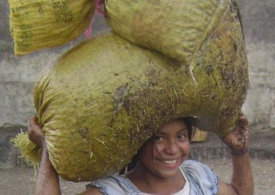 This girl carries two gunny-sacks of coffee but still smiles in the Finca Pampojilá.