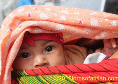 This baby ofEl Tejar, Chimaltenango interacts with the worth while riding on mother's back.