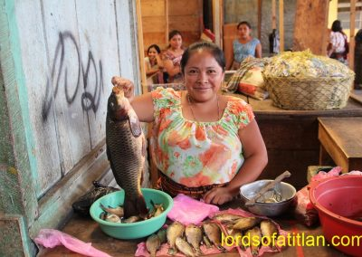 Fish vendor in addition to onlooker behind in market of San Pedro la Laguna