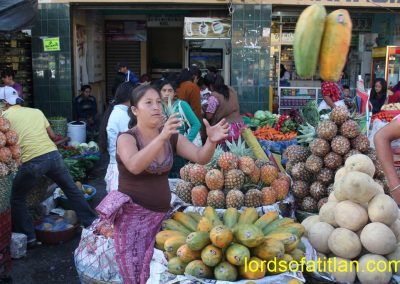 Woman from San Sebastián  catching airborne papayas. although San Sebastián is even more noted for its pineapples.